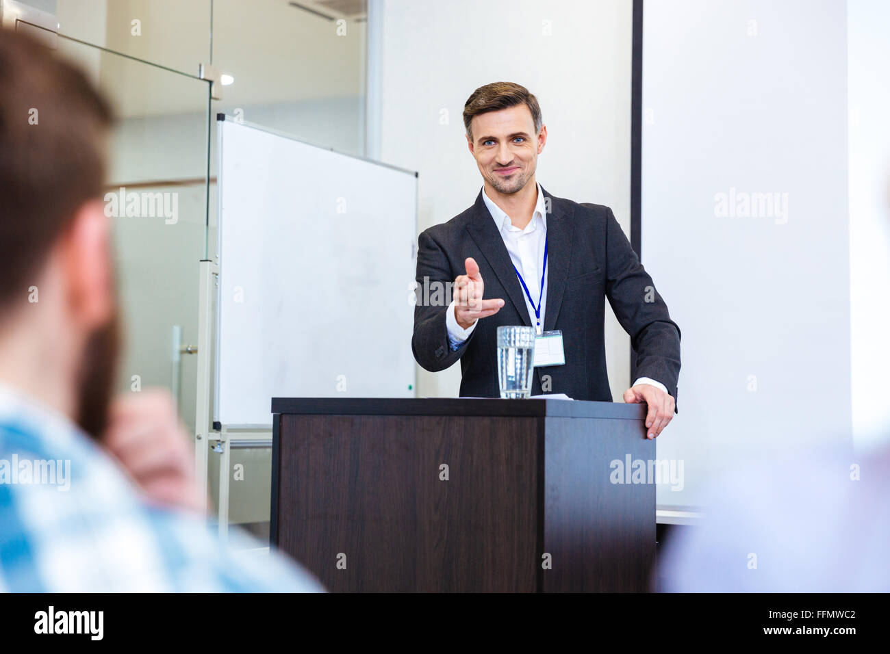 Smiling handsome businessman standing at tribune in conference hall and pointing in audience - Stock Image