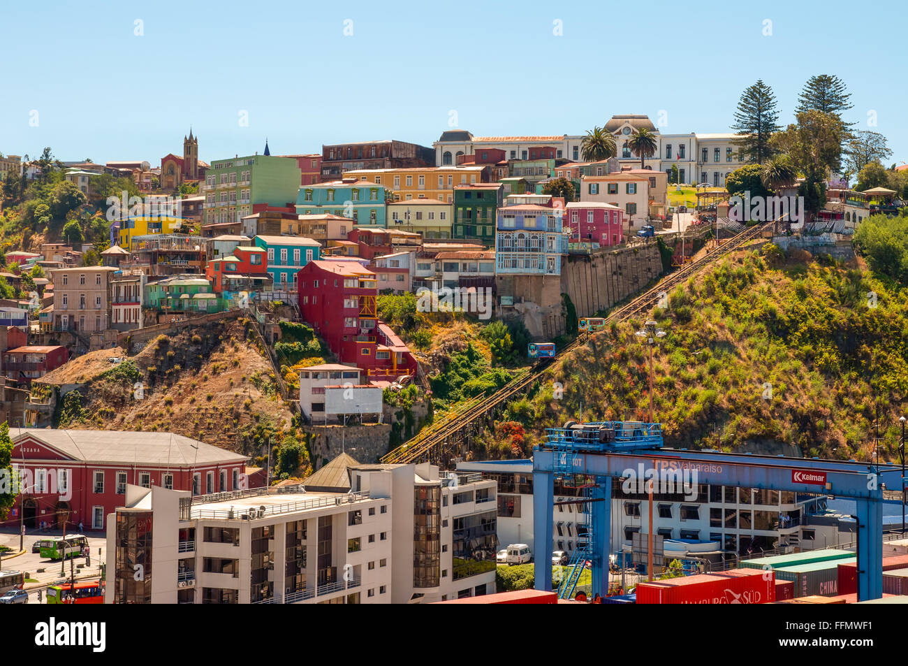 Two cars of Funicular in Valparaiso, Chile against background of colorful houses. - Stock Image