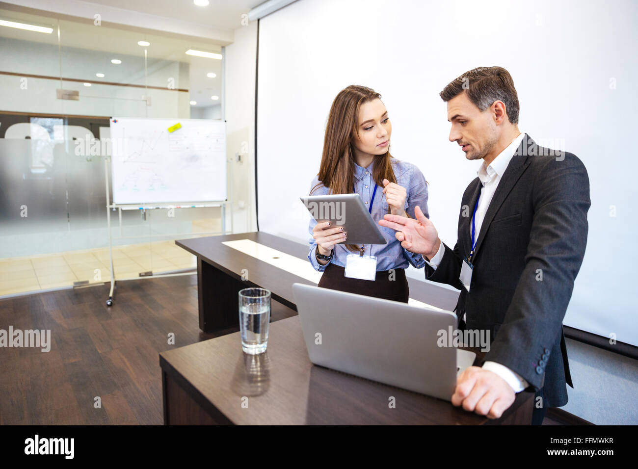 Businessman and his secretary standing and planning work in office - Stock Image