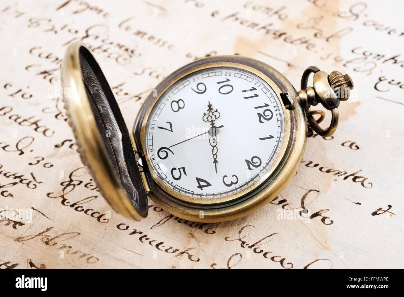 Vintage pocket watch over manuscript background - Stock Image