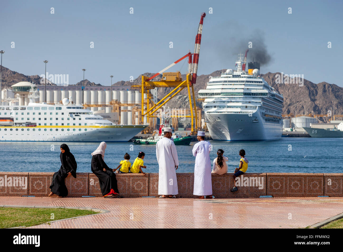An Omani Family Watch The Cruise Ships Leaving The Port At Muttrah, Muscat, Sultanate Of Oman - Stock Image