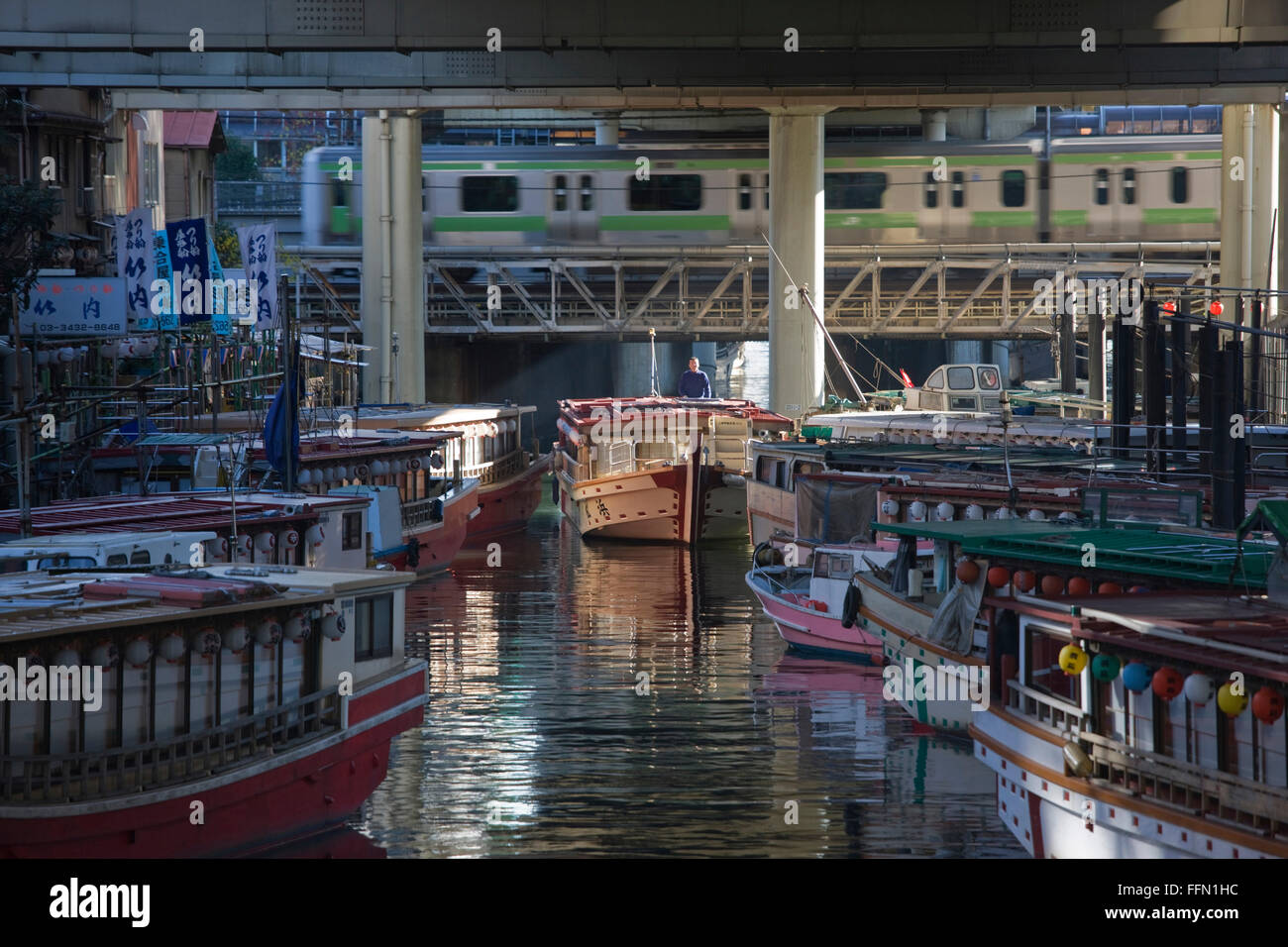 With a city commuter train rushing past in the background a boat captain eases his yakatabune excursion houseboat - Stock Image