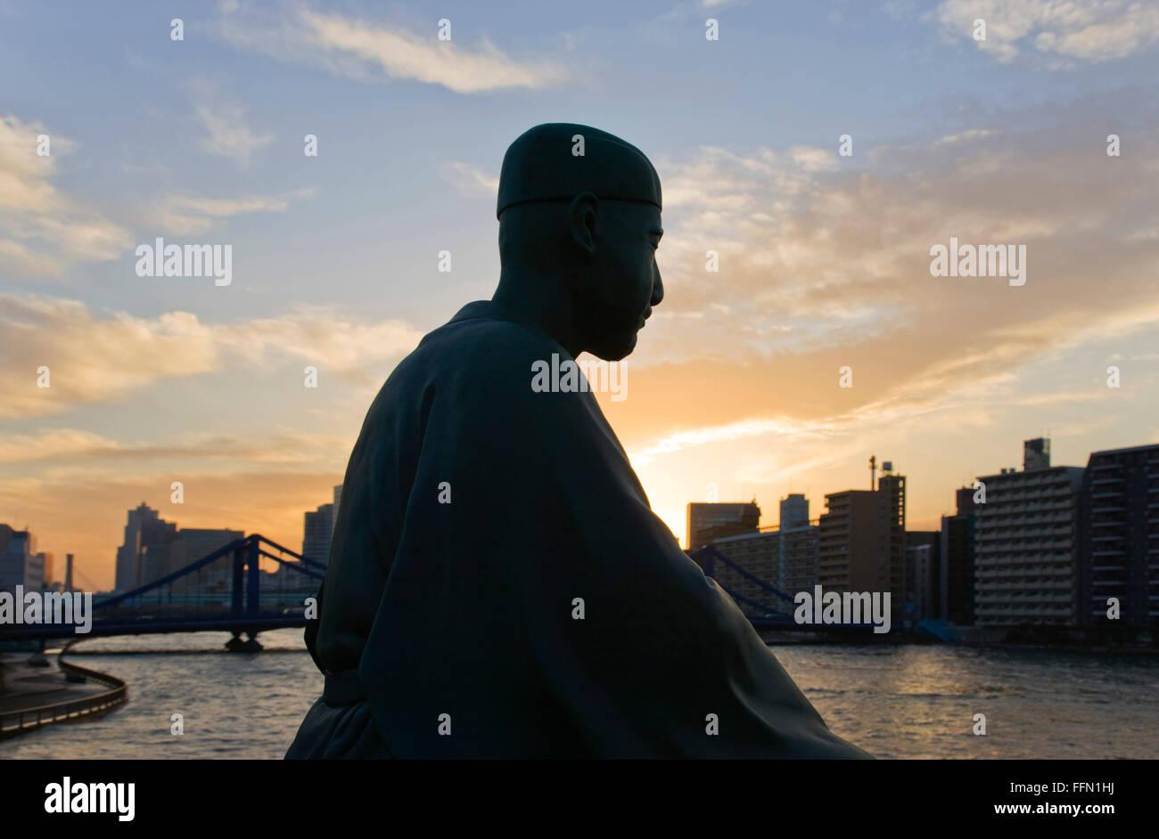A statue of Matsuo Basho (Japan's most renowned haiku poet) overlooks the Sumida River and Kiyosubashi Bridge - Stock Image