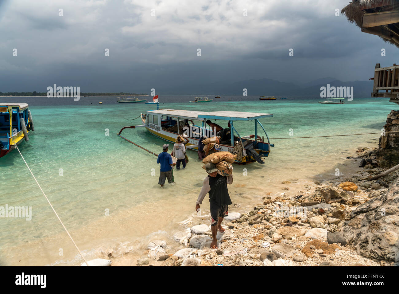 worker carrying construction materials to the small island Gili Meno, Lombok, Indonesia, Asia - Stock Image