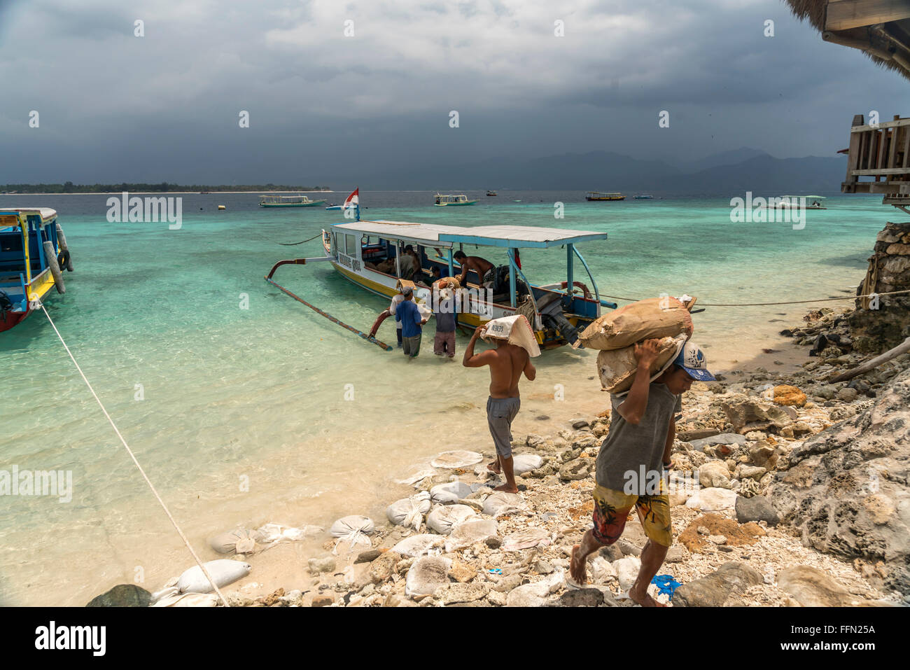 workers carrying construction materials to the small island Gili Meno, Lombok, Indonesia, Asia - Stock Image