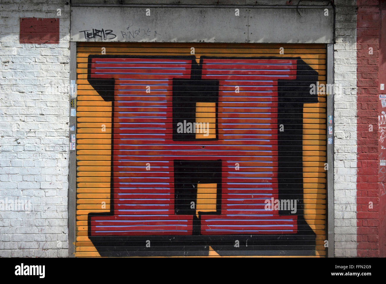 Ben Eine. Street art, a large initial E painted on metal scrolling shutters. - Stock Image