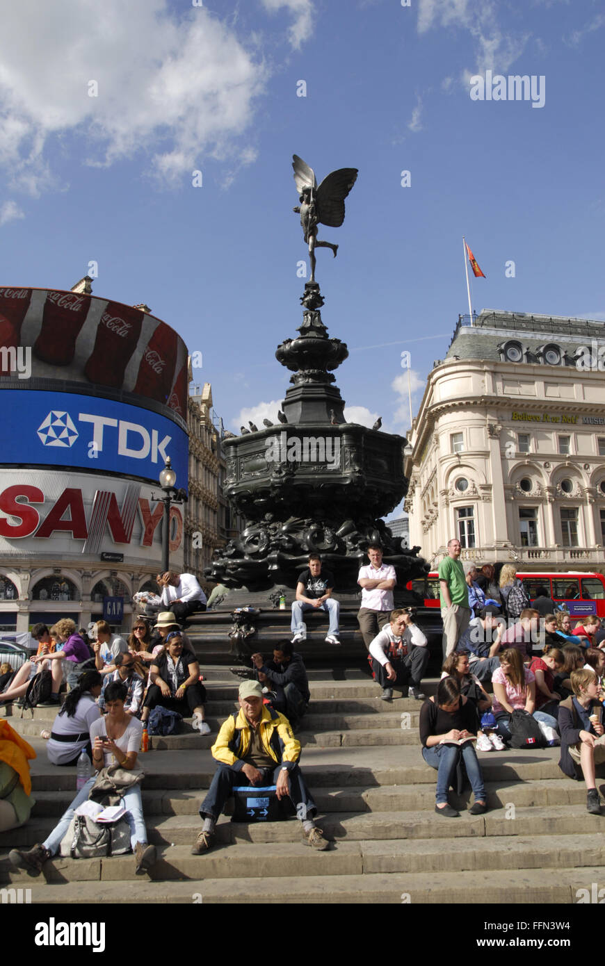 Eros at Picadilly Circus, London, with tourists sitting on the steps. - Stock Image