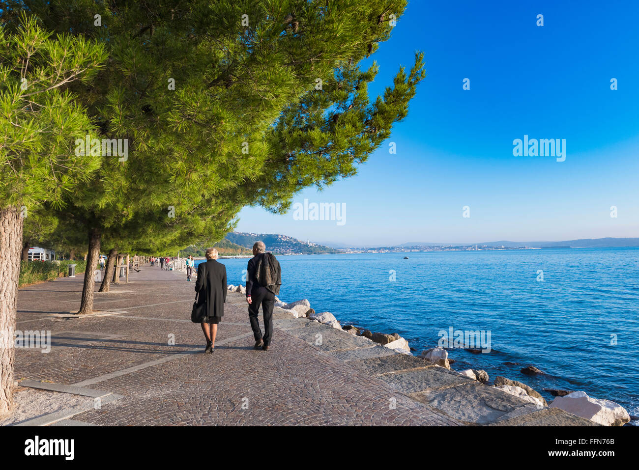 Couple walking along the Promenade along the Adriatic Sea coast at Trieste, Italy, Europe - Stock Image