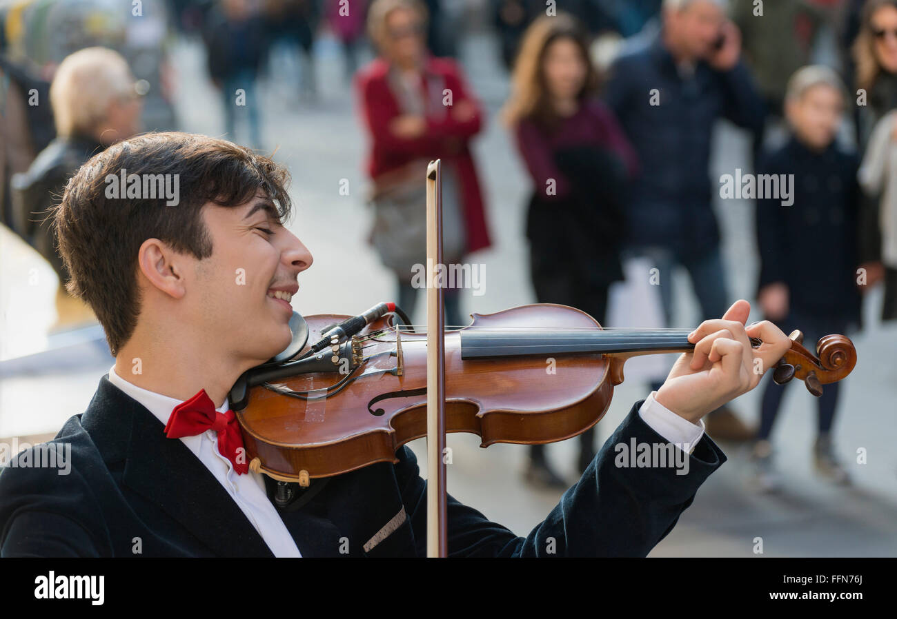 Street musician performer playing a violin on the busy Via Toledo in Naples, Italy, Europe - Stock Image