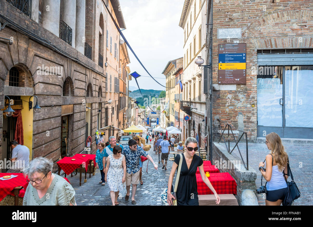 street view with tourists in Urbino, Italy. - Stock Image