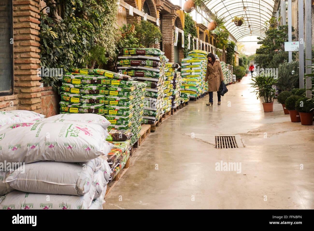Woman at Garden centre, offering plants, compost, fertilizers, Spain. - Stock Image