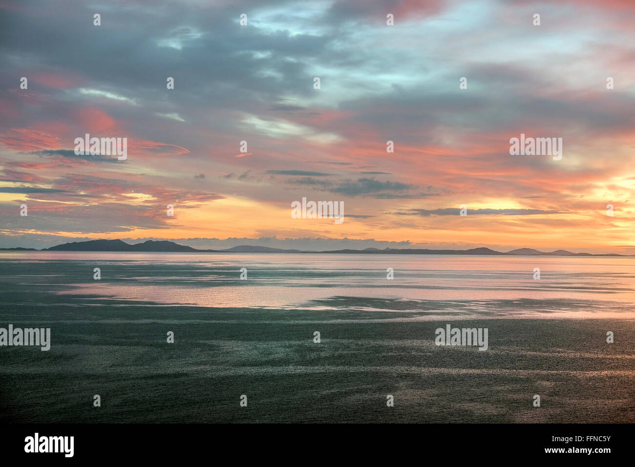 the minch sunset with complex sky and outer hebrides uists on horizon from duntulm trotternish - Stock Image