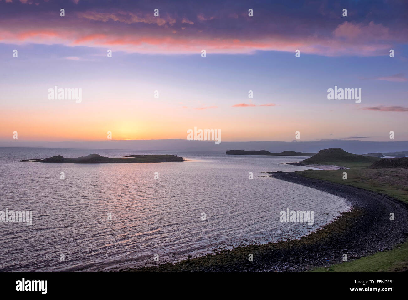 magenta sunset over coral beach at loch dunvegan with dusky islets - Stock Image
