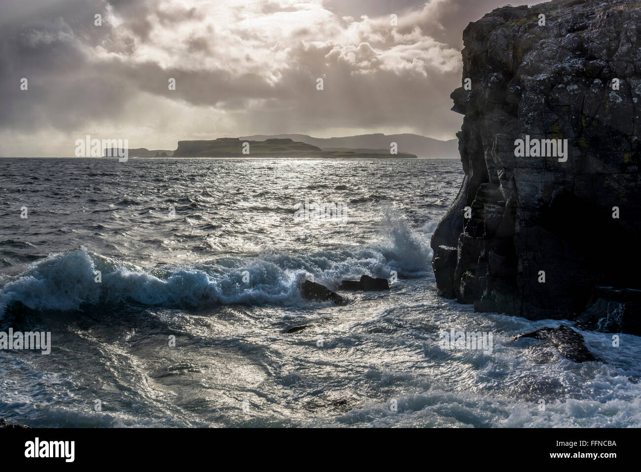 surf at coast with waves looking to duirinish with cliff in storm - Stock Image