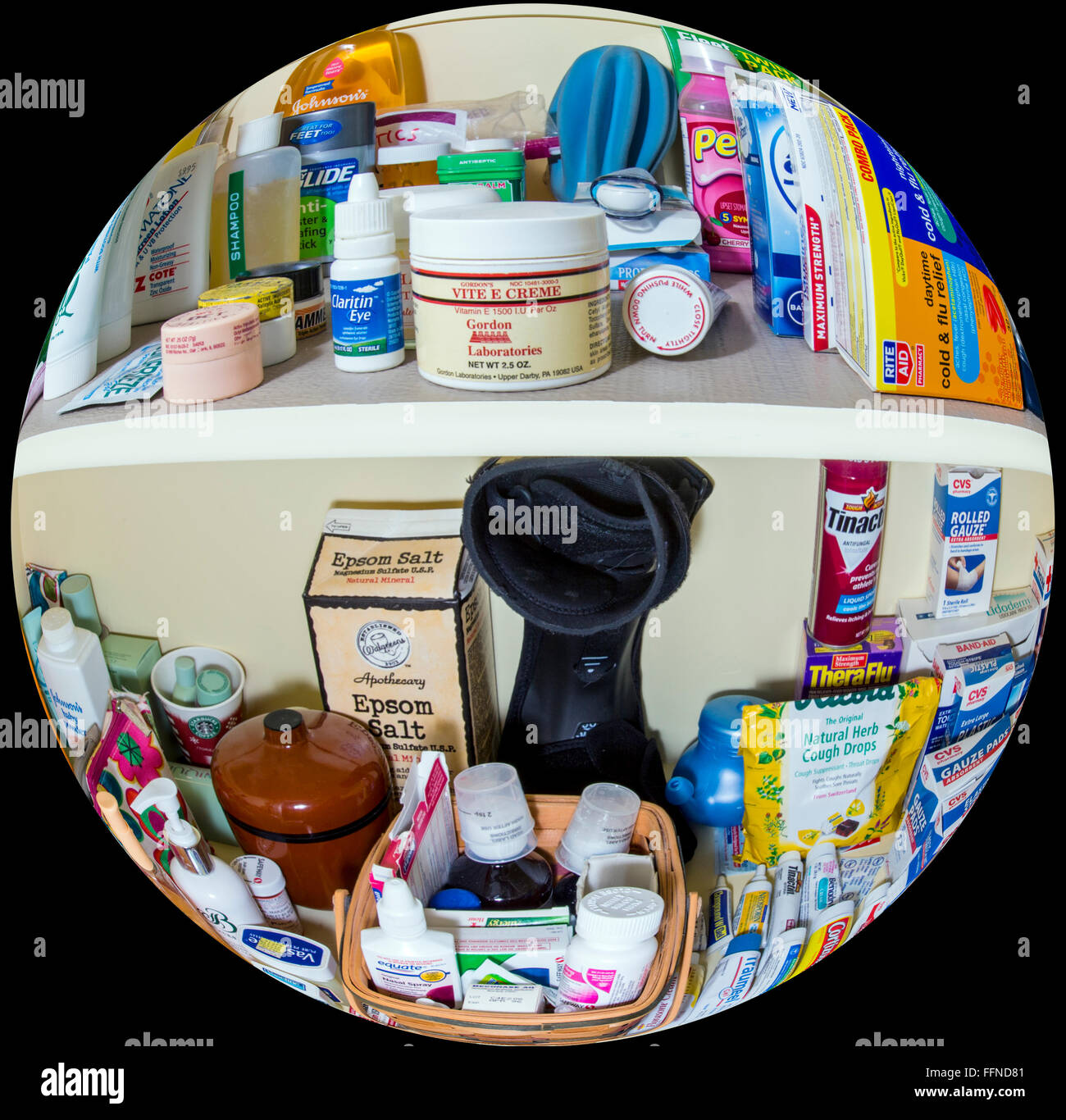 Fisheye view of home medicine cabinet shelves full of pharmaceuticals, drugs, balms, bandages, ointments and personals - Stock Image
