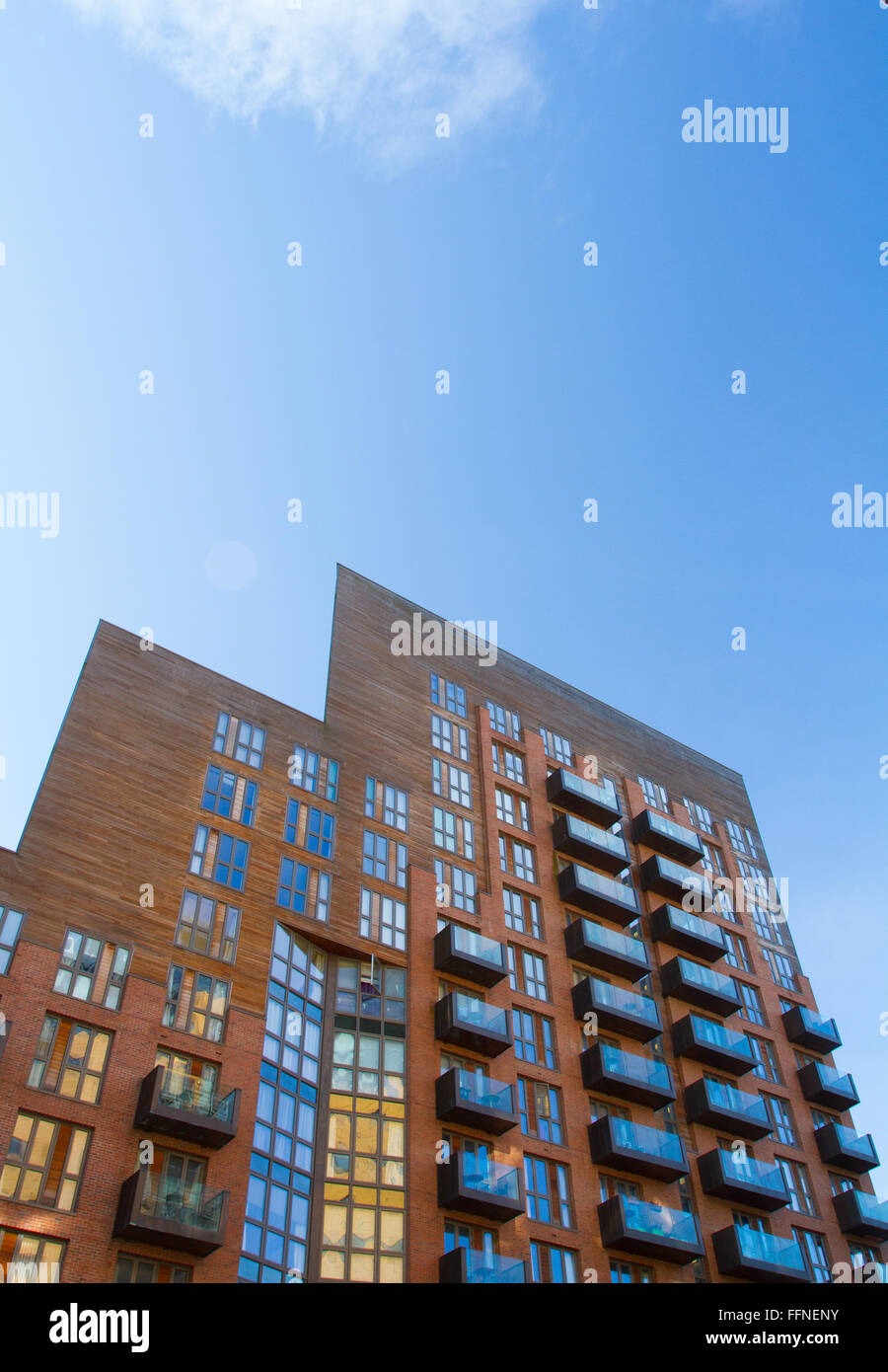 A view from the ground looking up to a tall skyscraper under a blue sky. Angular lines of architecture with uniformity. - Stock Image