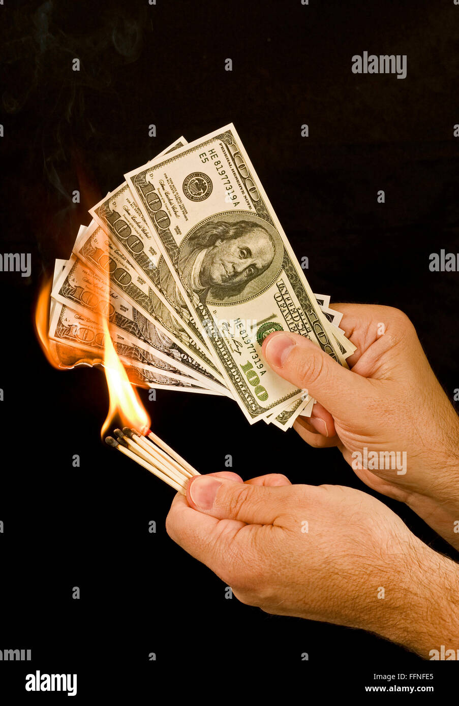 Money to Burn 1.  A man uses matches to set fire to a group of one hundred dollar bills. - Stock Image