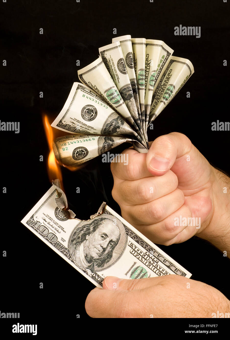 Money to Burn.  A man uses a one hundred dollar bill to set fire to the hand full of one hundred dollar bills in - Stock Image