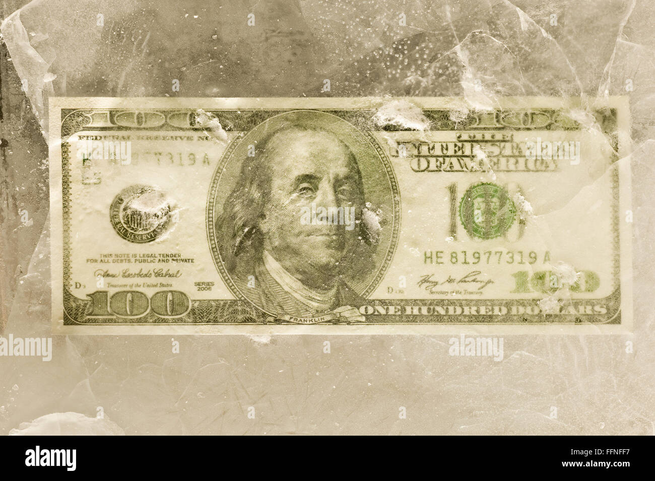 One Hundred Dollar Bill Behind Cracked Ice - Stock Image