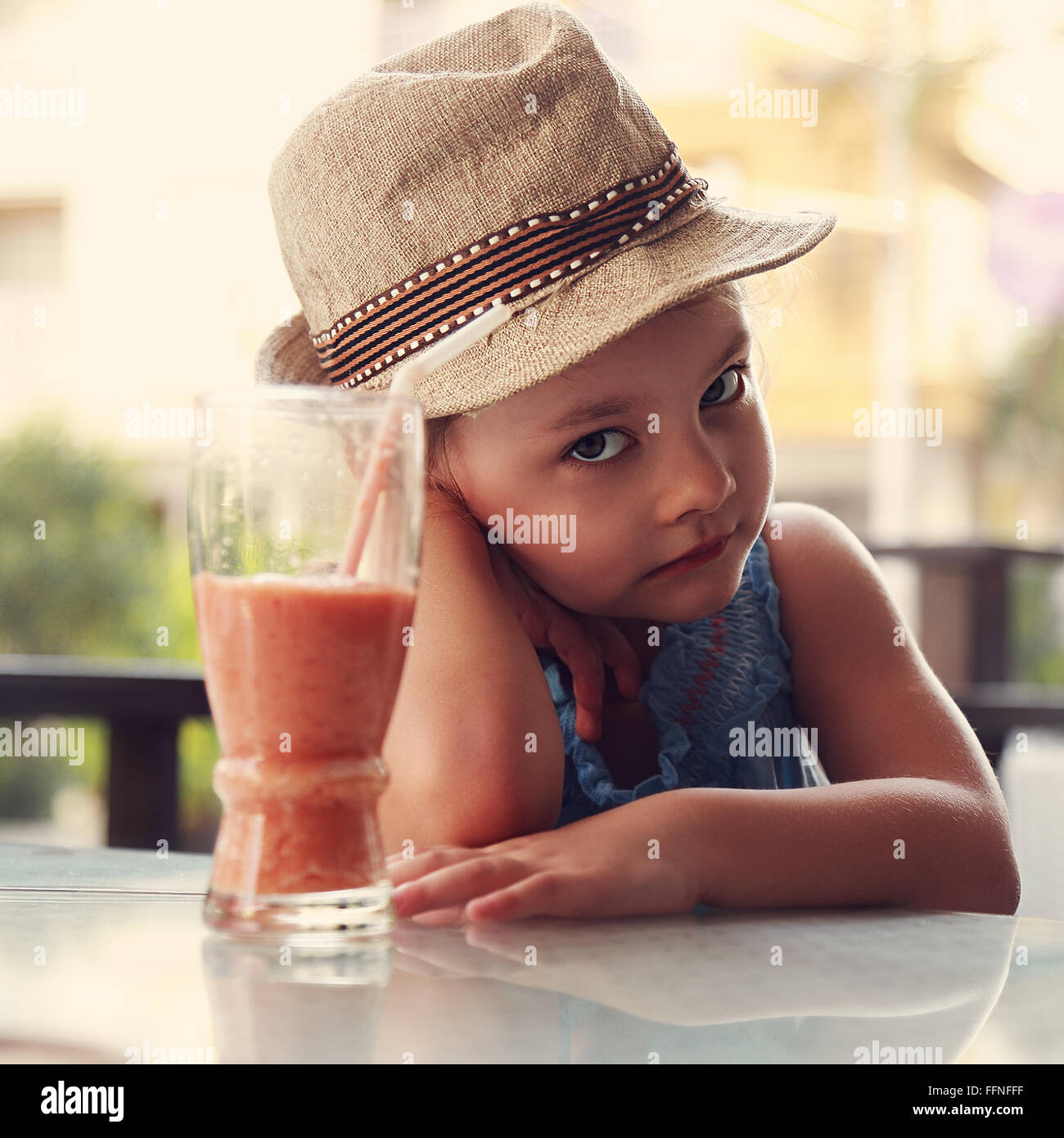 Alone unhappy kid girl sitting in restaurant and does not want to drink healthy juice on summer background - Stock Image