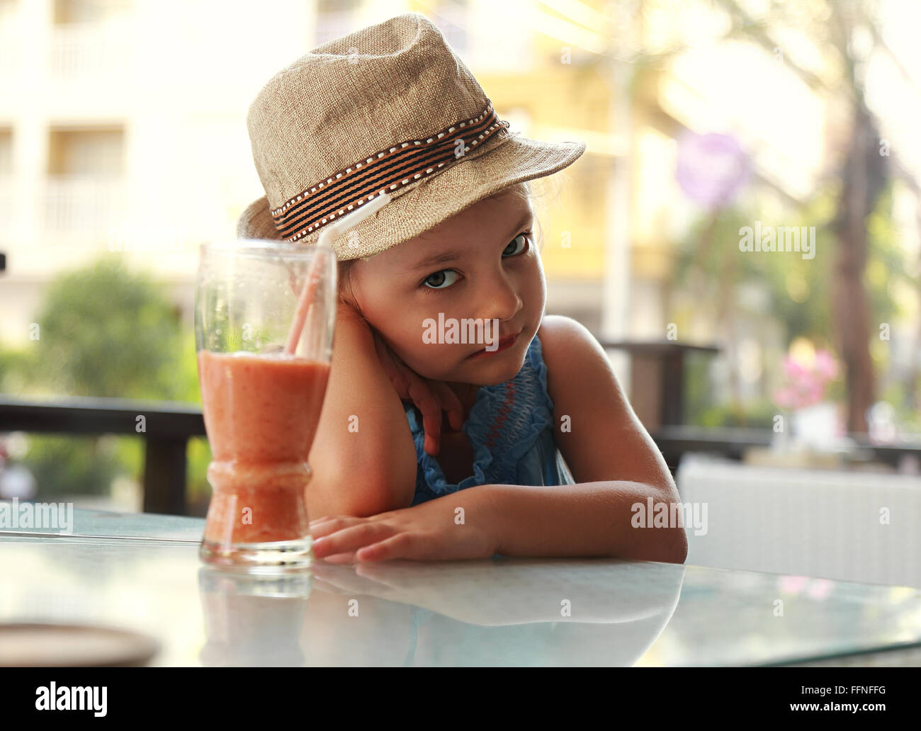 Cute unhappy kid sitting in restaurant and not want to drink healthy juice on summer background - Stock Image