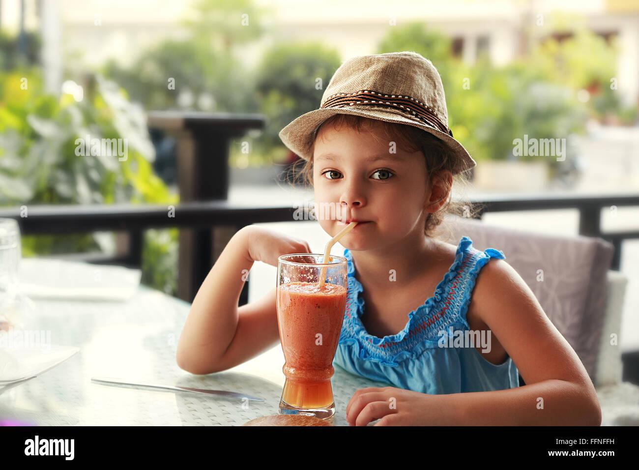 Fun kid girl in fashion hat drinking smoothie juice in street restaurant - Stock Image