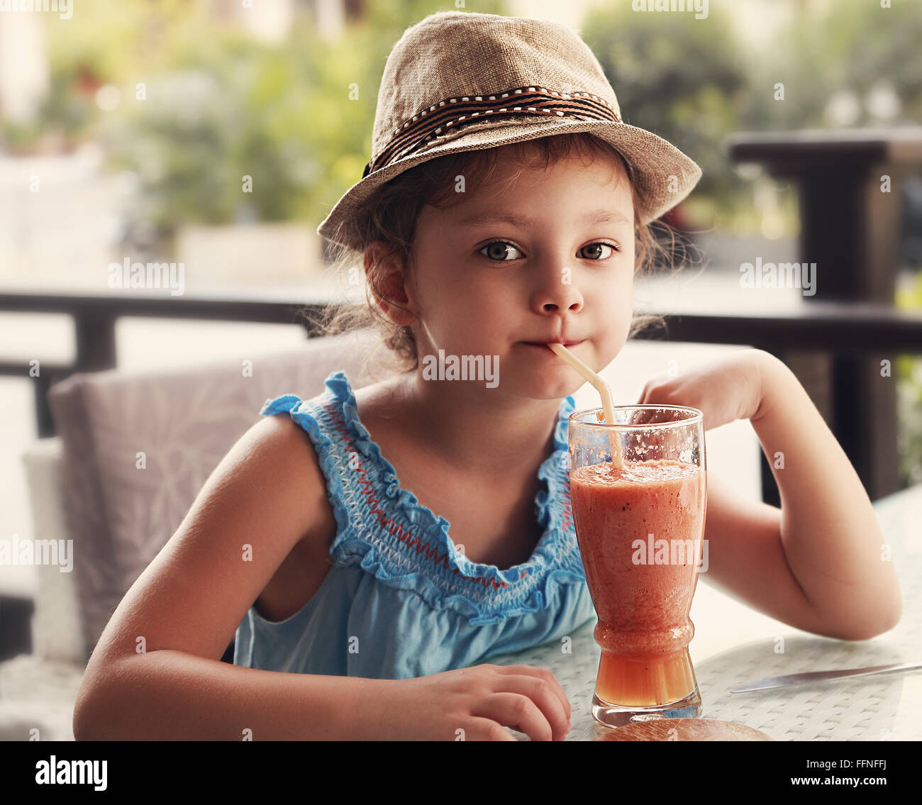 Fun kid girl in fashion hat drinking smoothie juice in street restaurant. Toned closeup portrait - Stock Image
