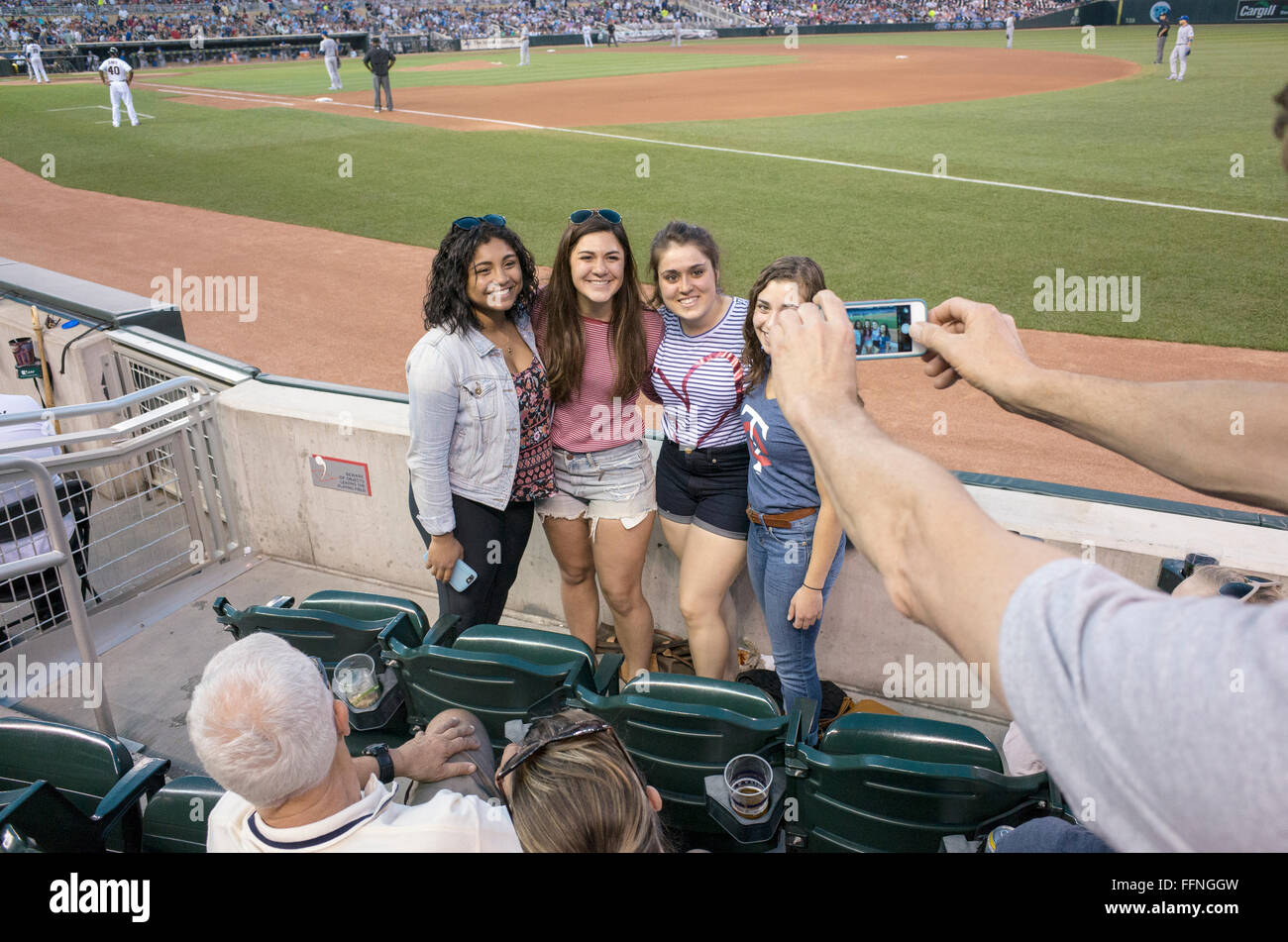 Four teenage women having their photo taken with a cell phone at Minnesota Twins baseball game. Minneapolis Minnesota - Stock Image