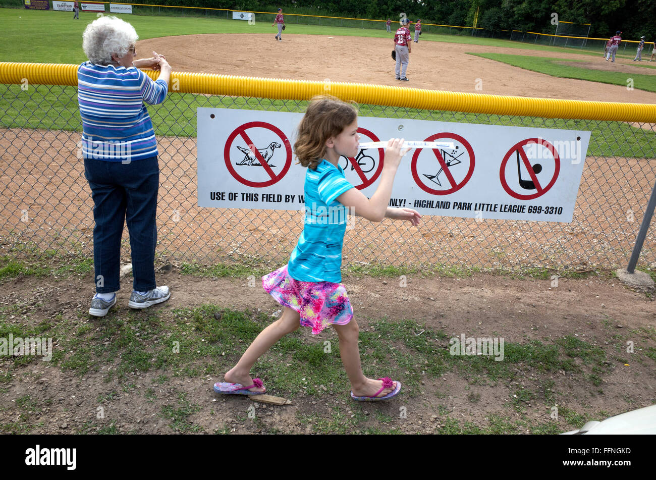 Young girl walking by ballpark warning signs eating frozen treat oblivious to game in progress. St Paul Minnesota - Stock Image