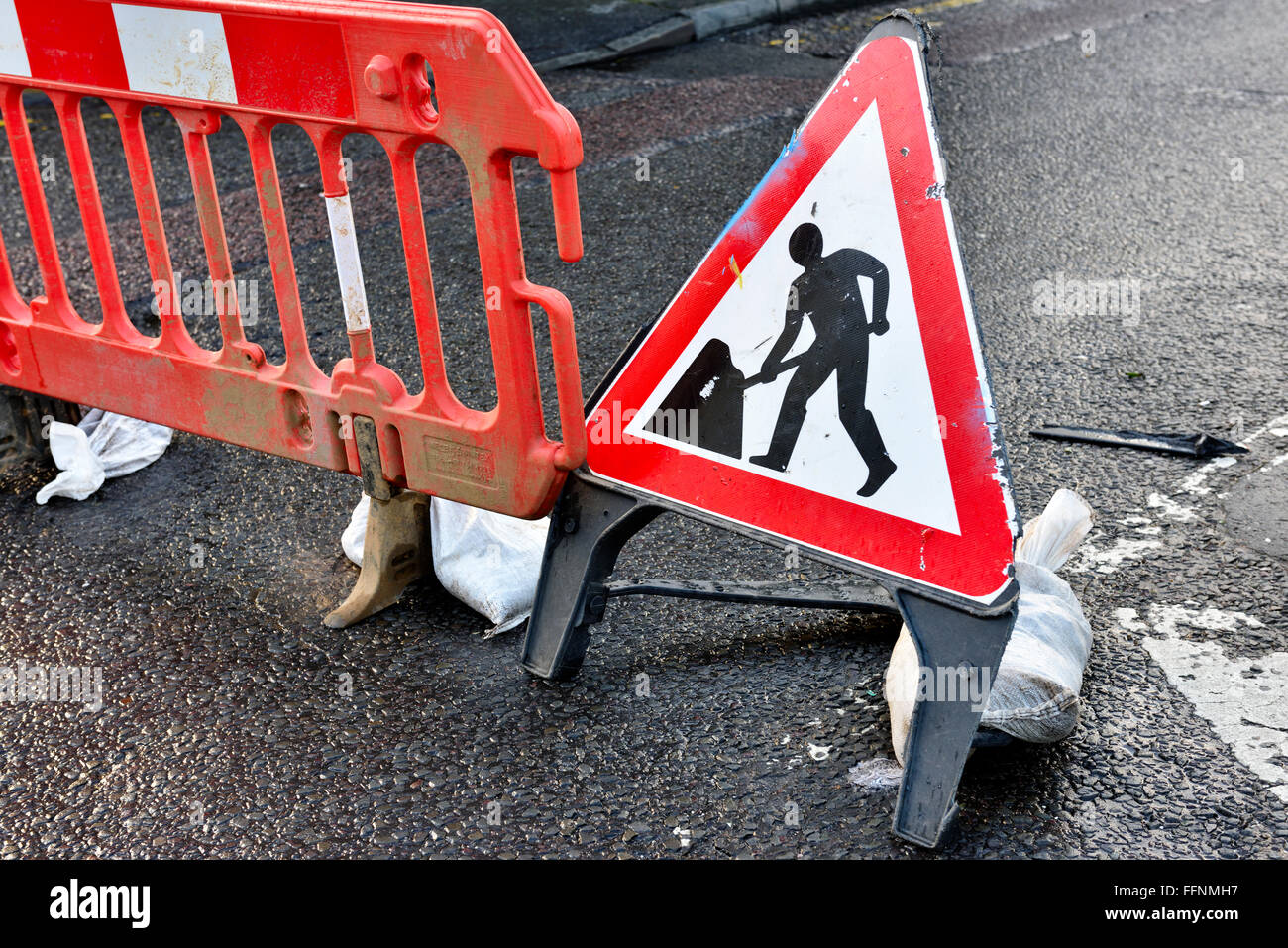 Sign men working and barrier across road - Stock Image