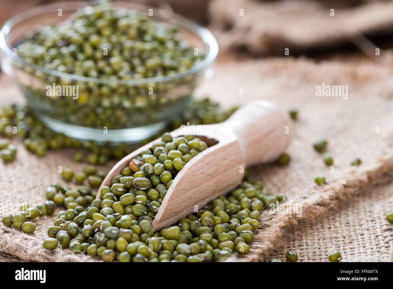 Some Mung Beans on an old wooden table (close-up shot) - Stock Image