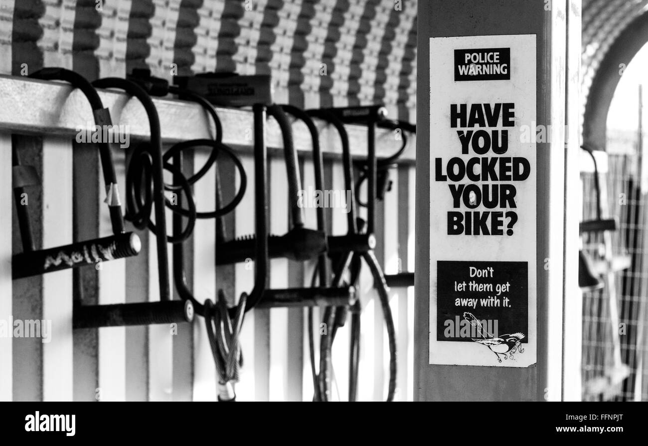 A 'Have you locked your bike?' sign warning about bike theft in front of bike locks locked around a bike - Stock Image