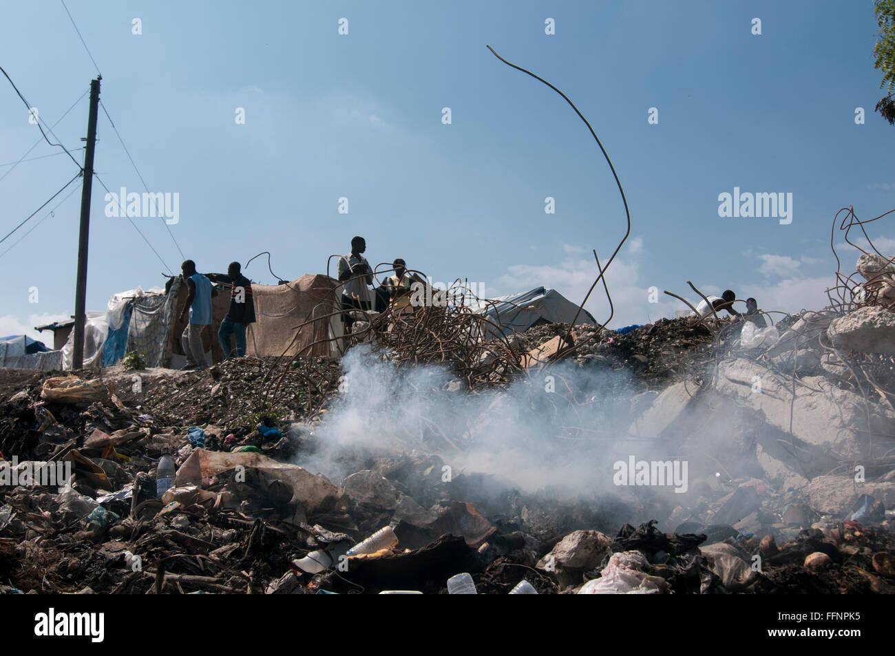 A dump with burning garbage at a makeshift camp set up for survivors of a 7.0 magnitude earthquake which struck - Stock Image