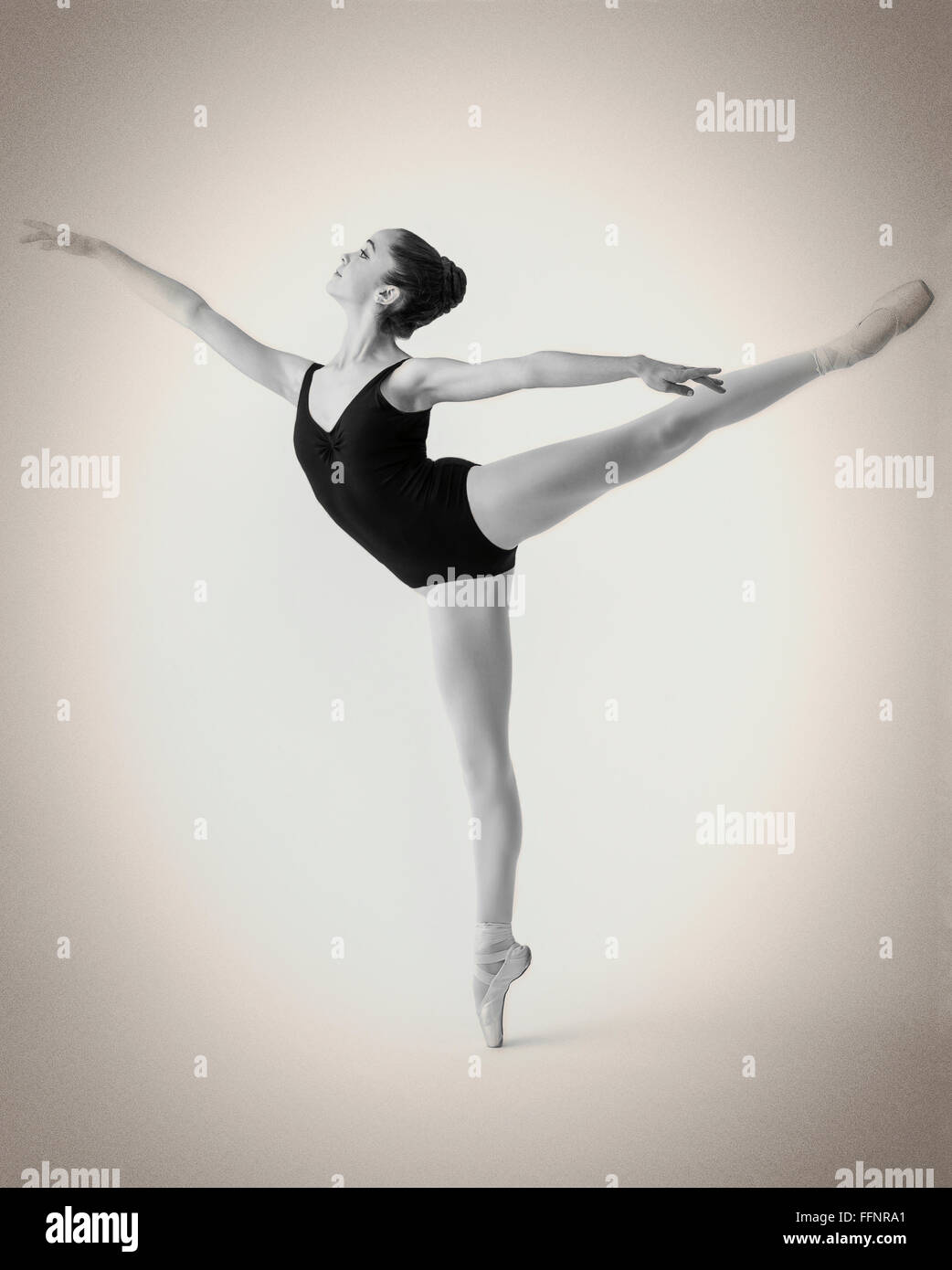 Black & white studio photograph of female teenage ballerina dancer performing an arabesque - Stock Image