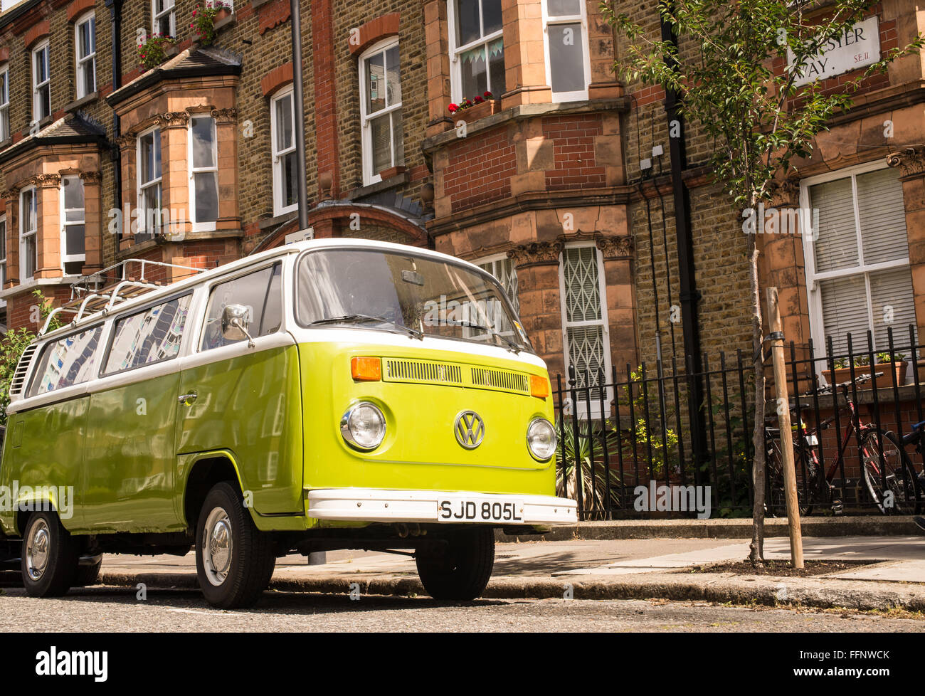 Old vintage green van parked in a street with Victorian houses in the background - Stock Image