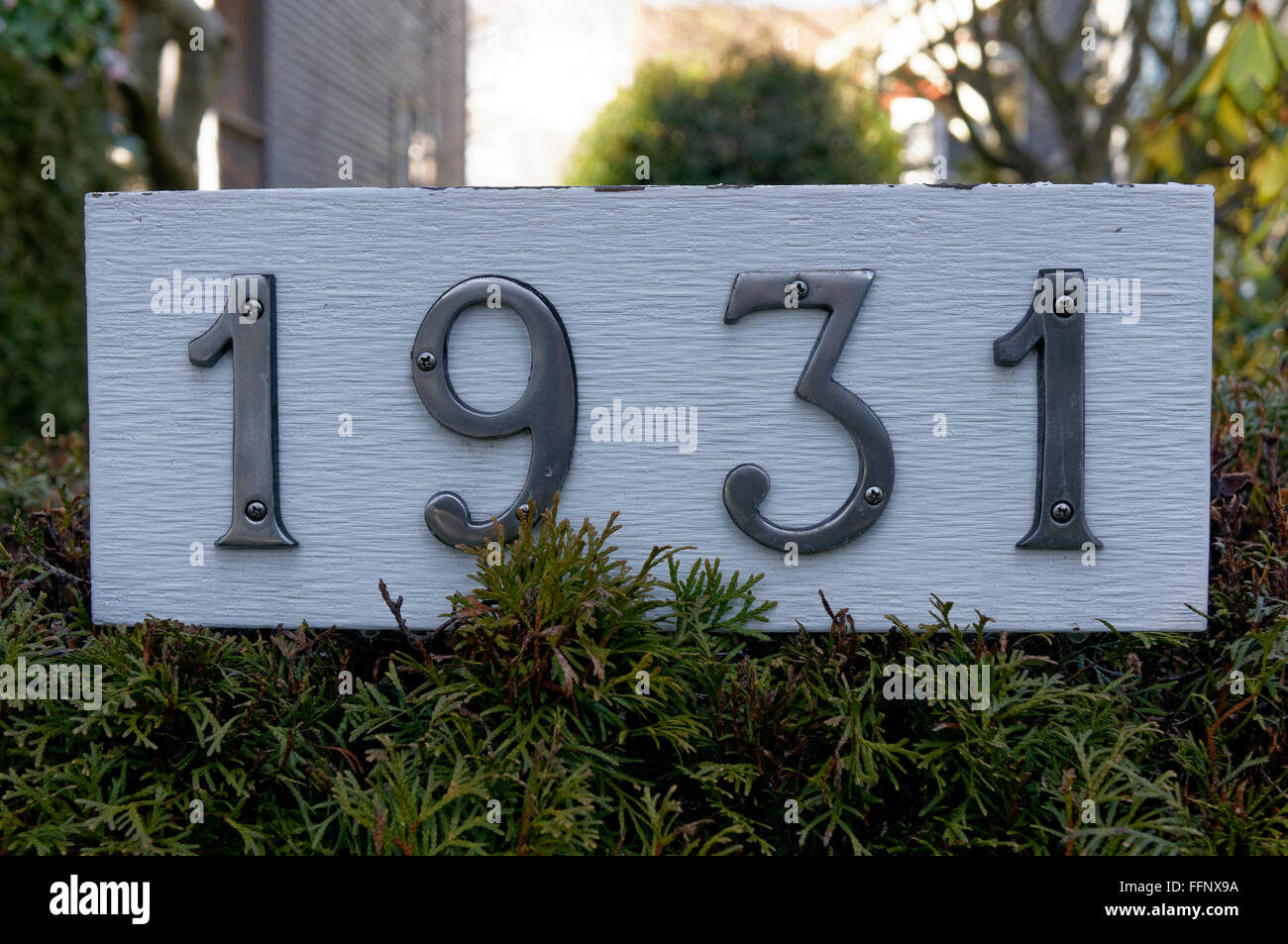 1931 metal house number on a white wooden background - Stock Image