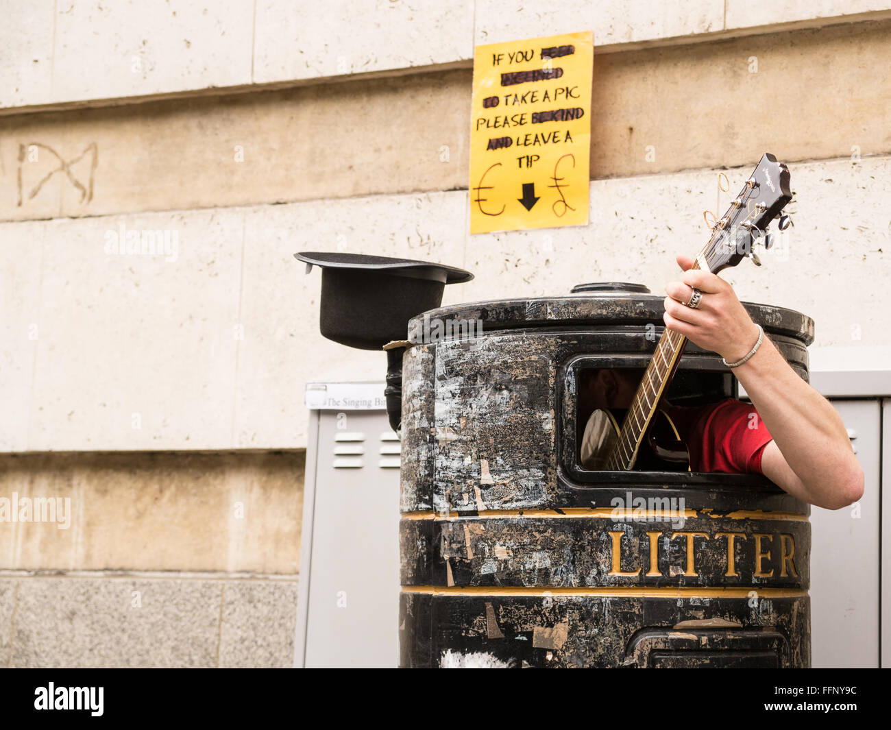 Busker singing and playing guitar inside a rubbish bin on a street. - Stock Image