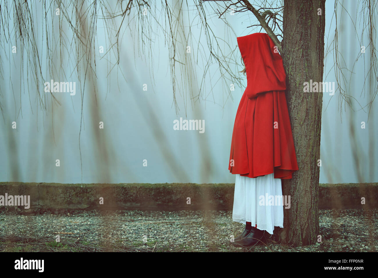 Woman with red cloak in misty and foggy day . Sadness conceptual - Stock Image