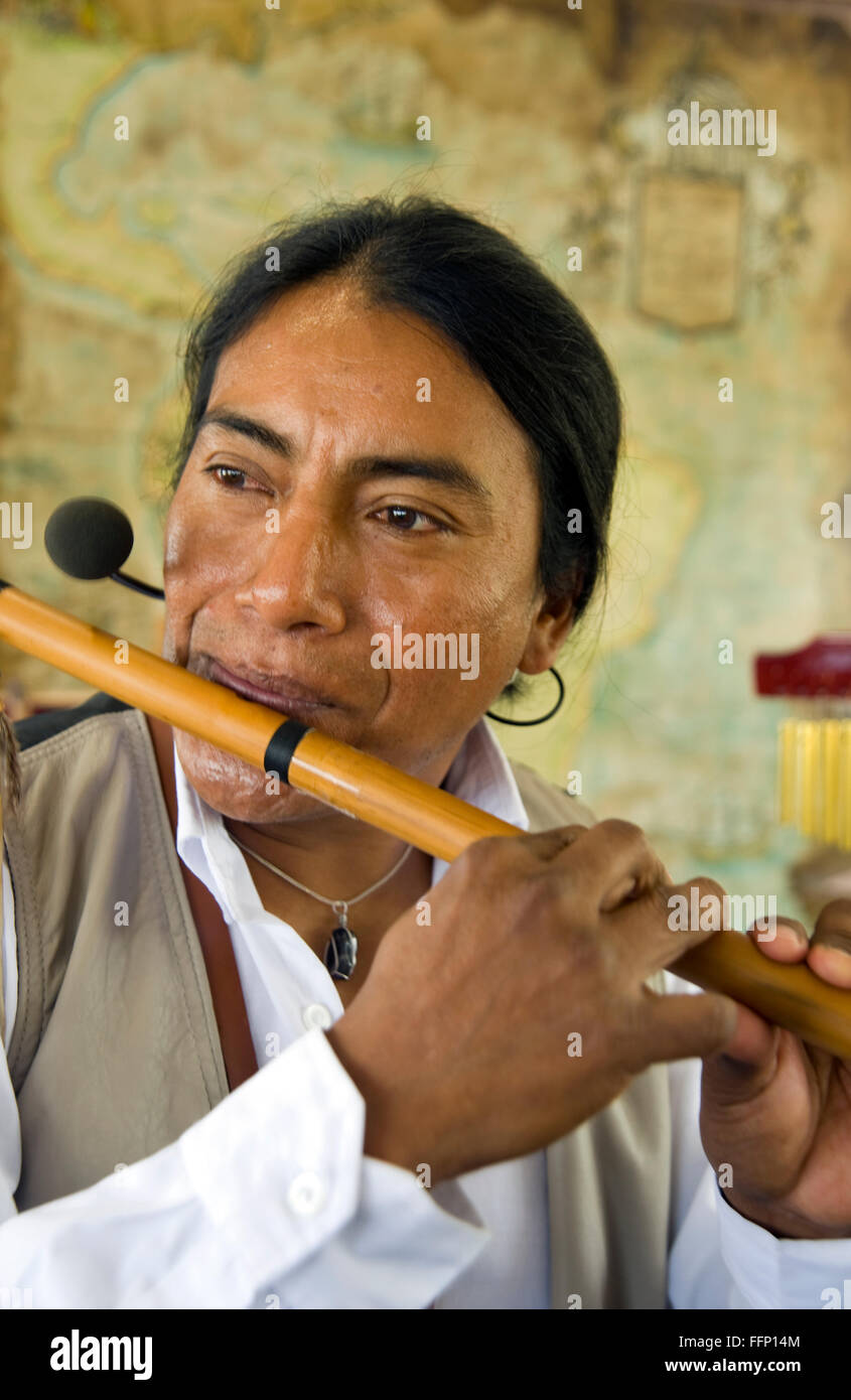 Ecuadoran musician playing a flute in the Amazon river region - Stock Image