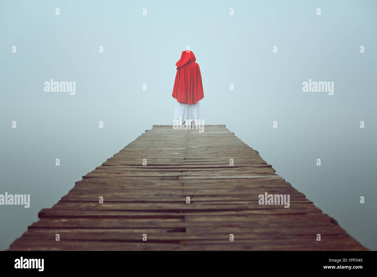 Red hooded woman looks at foggy lake on a wooden pier . Sadness and loneliness concept - Stock Image