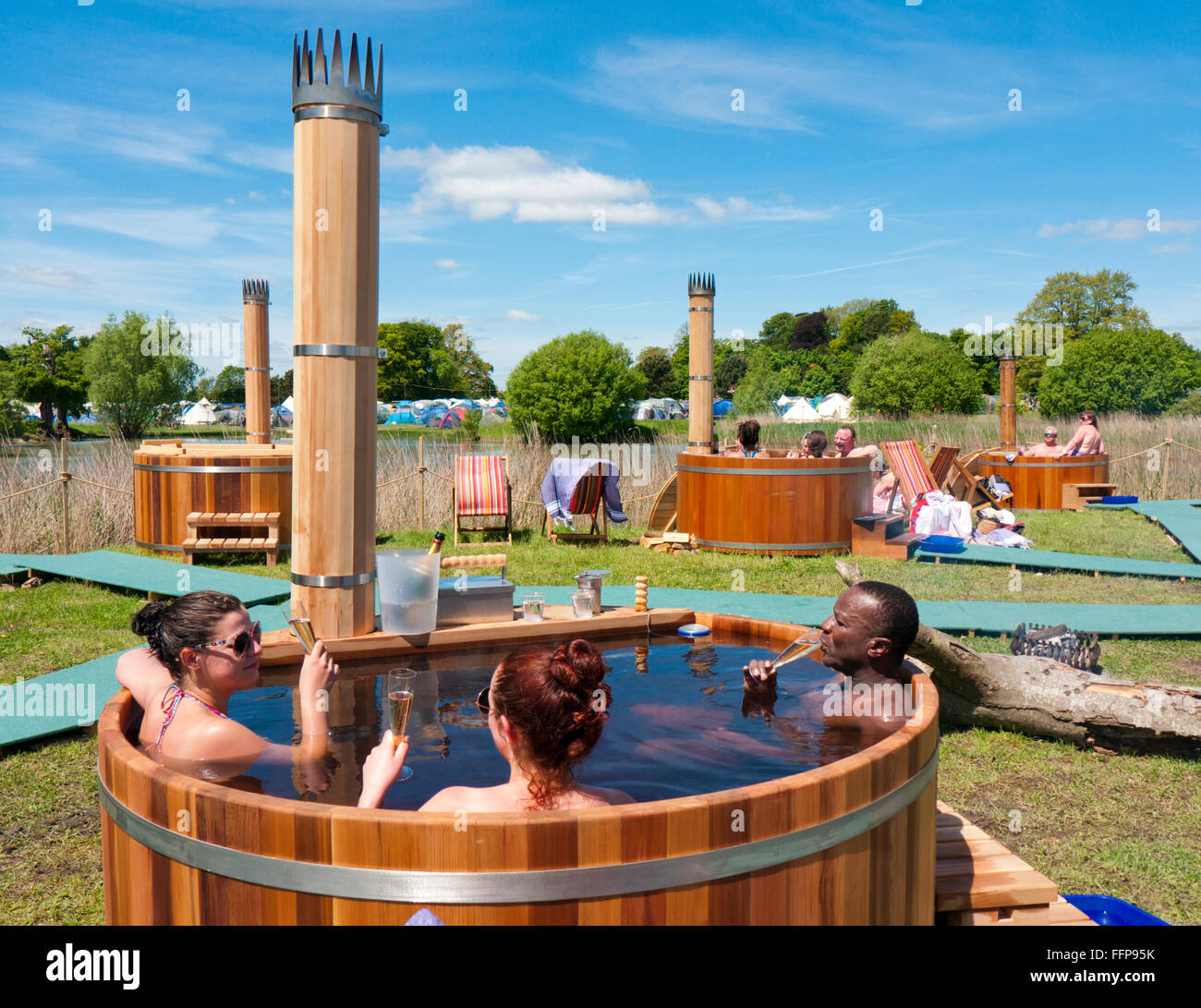 People drinking champagne in a hot tub powered by a built in wood burner at a festival in Britain Stock Photo