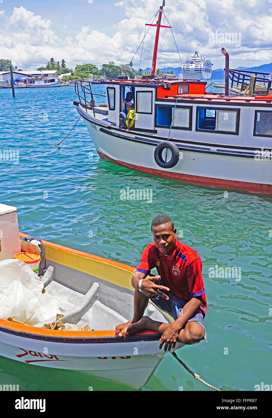 Young man on boat at Alotau Harbour on Milne Bay, Papua New Guinea. - Stock Image