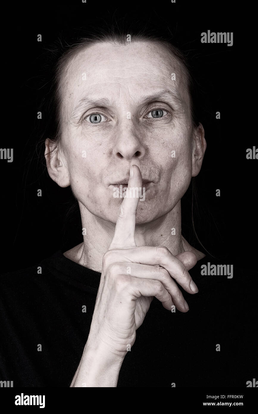 Portrait of an attractive adult woman putting the finger in front of the mouth and saying 'Hush!' - Stock Image