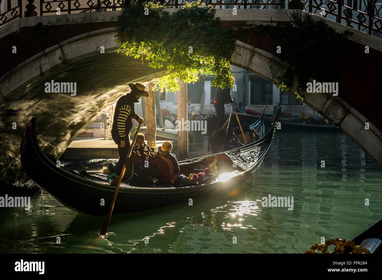 Canal, gondola with gondolier travels under a bridge, Venice, Veneto, Italy - Stock Image
