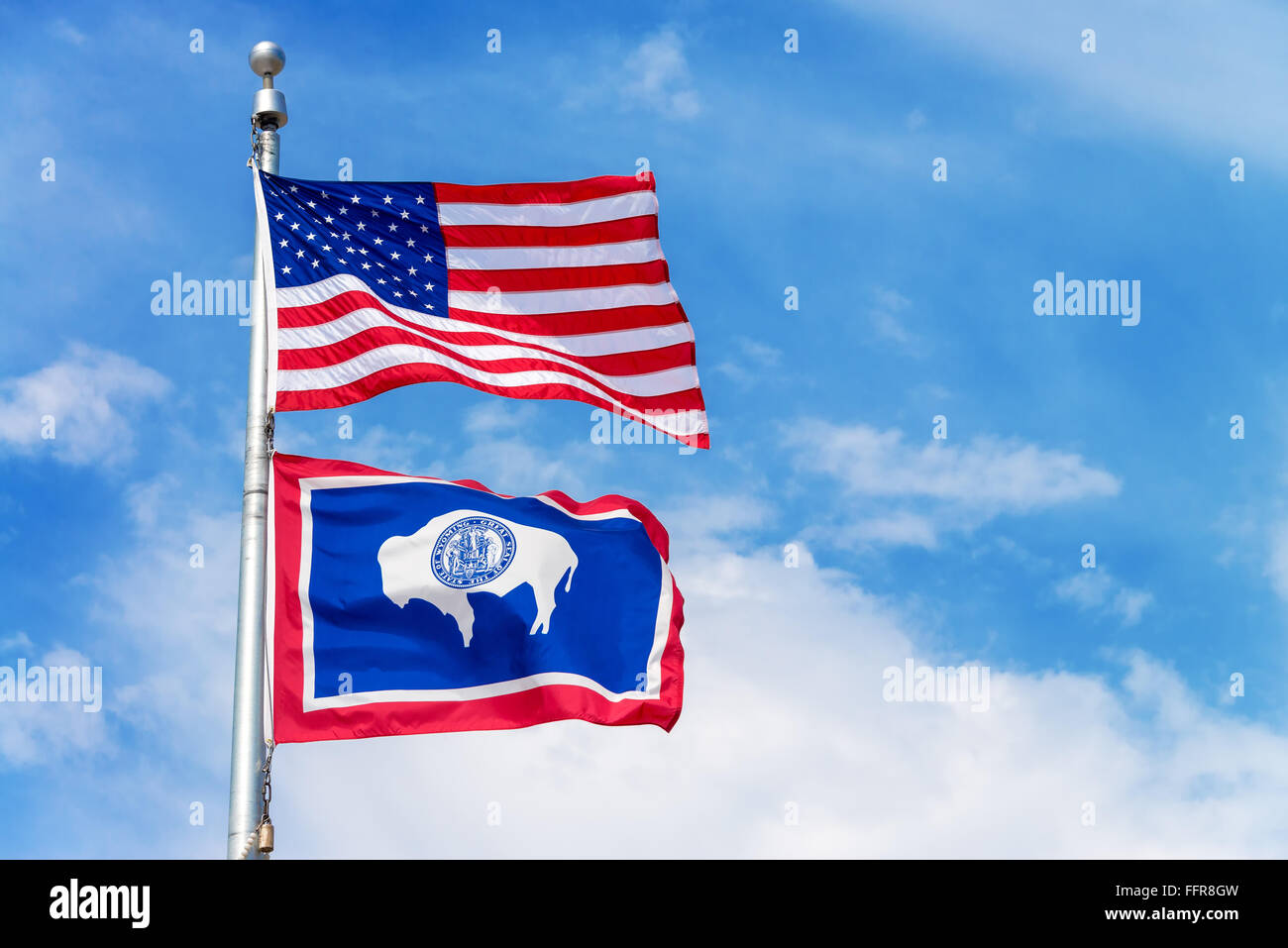 American flag flying a flag pole with the Wyoming state flag - Stock Image