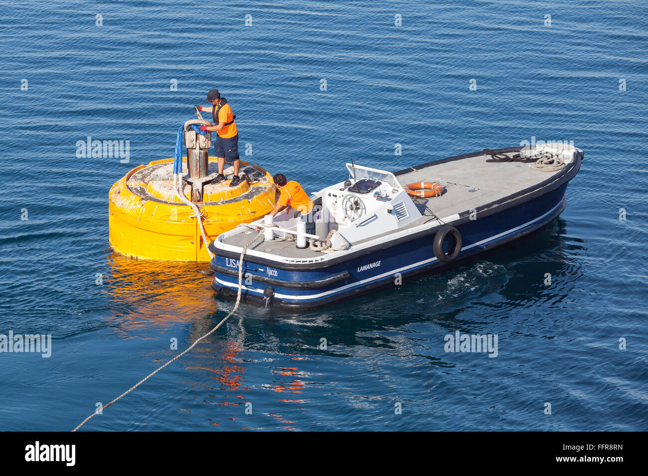 Ajaccio, France - June 30, 2015: Port operations, men at work. Motorboat is used for rope attachment on mooring - Stock Image