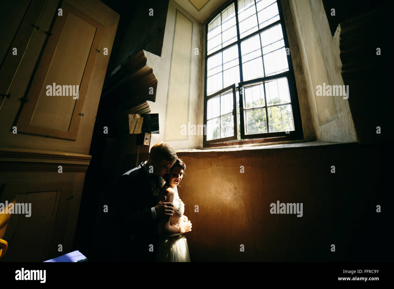 bride and groom on the background of a window. - Stock Image