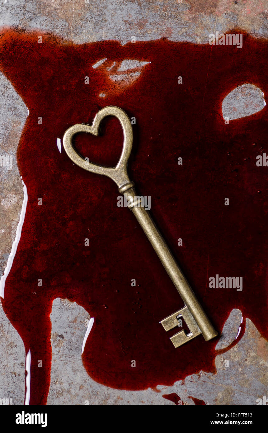Heart shaped key in a pool of blood - Stock Image