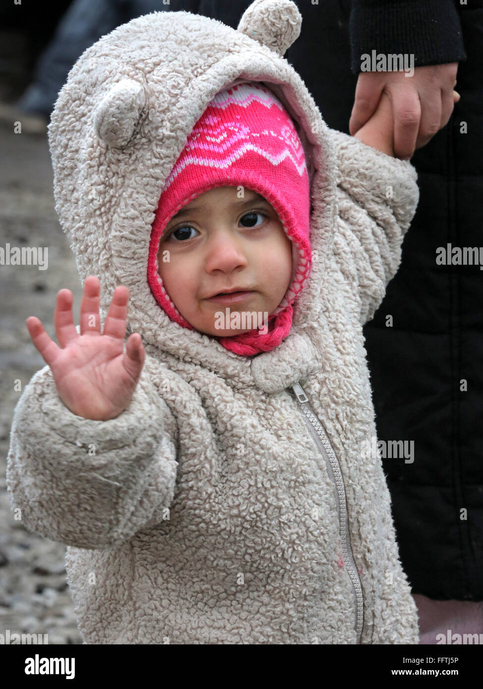 Portrait of a refugee girl (14 months) from Syria, now lives with her parents in the  tent camp 'Jungle' - Stock Image