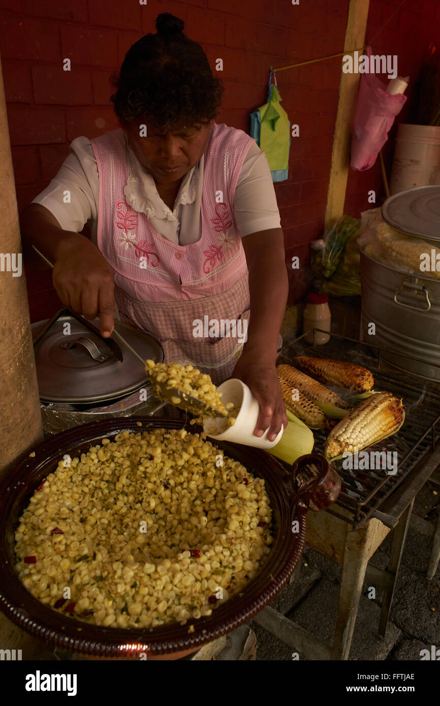 Mexican woman frying corn and fills it into a cup - Stock Image
